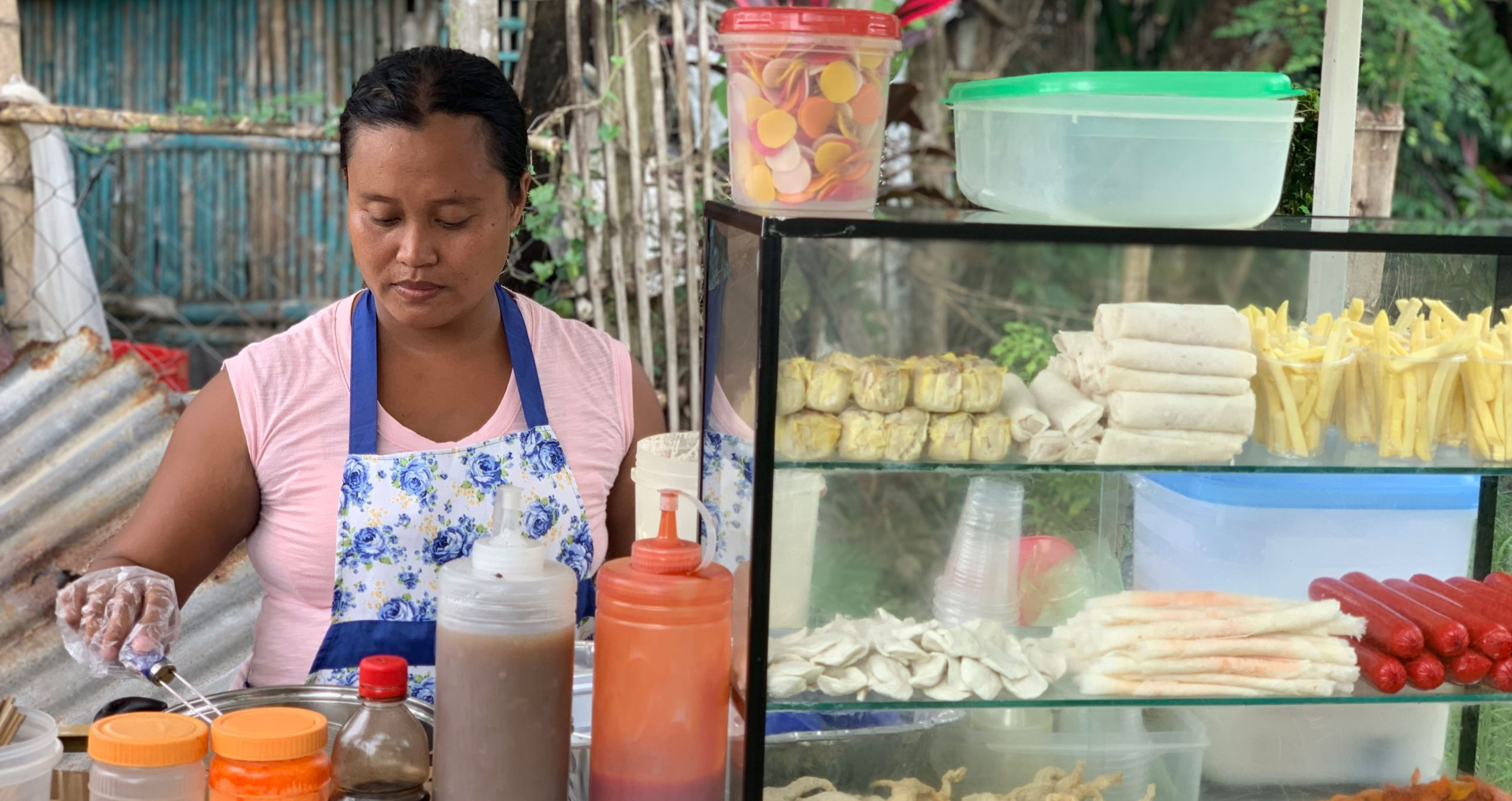 woman in Graduation program in Philippines works at her food stand