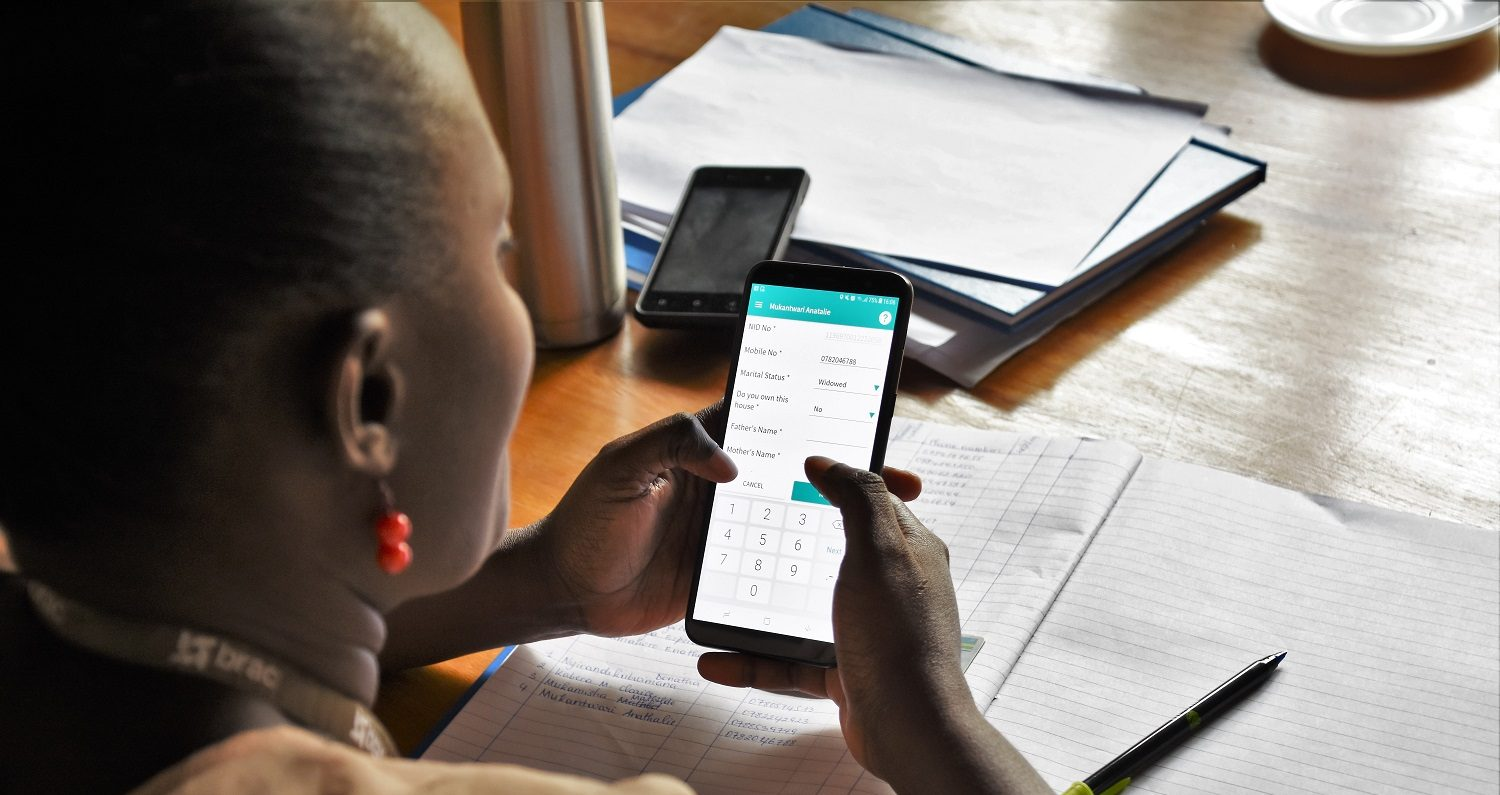 Women in Rwanda use a digital app on their phone to access their finances.