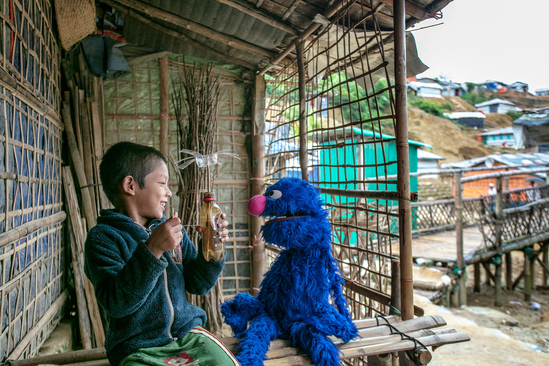 A Rohingya child plays with a muppet. Photo by Ryan Donnell for Sesame Workshop.