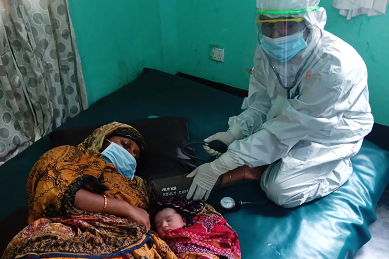 A BRAC community health worker wearing PPE cares for a mother and child