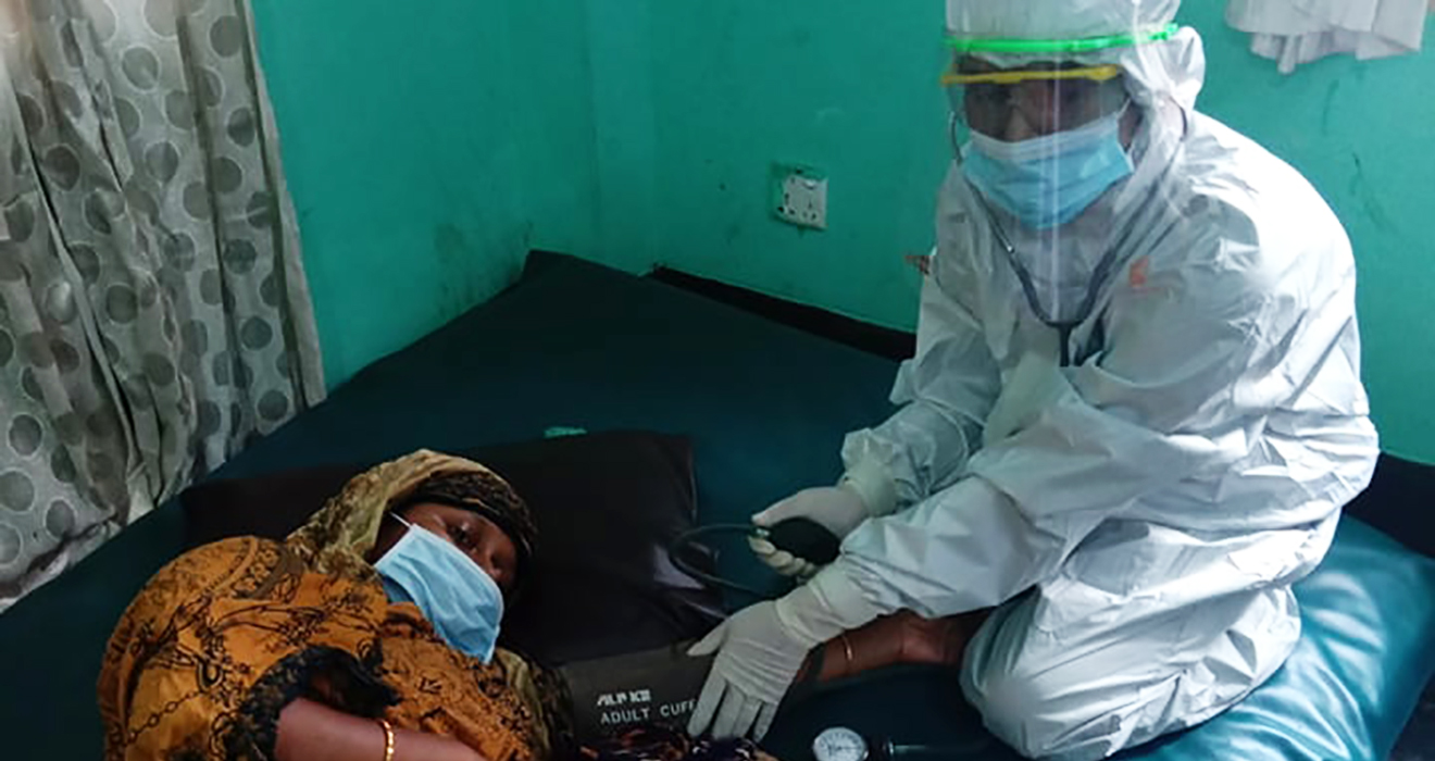 A BRAC community health worker wearing PPE cares for a mother