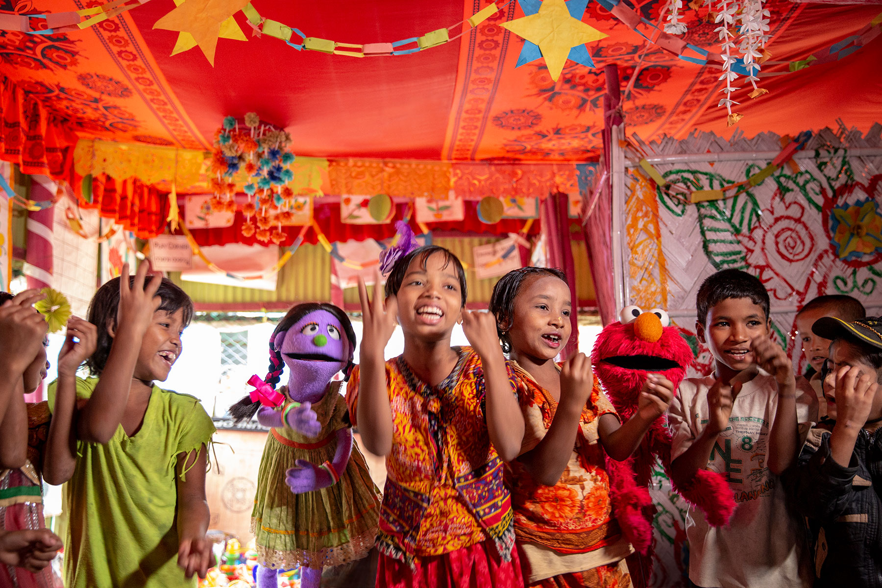 Rohingya children play with muppets in a BRAC Humanitarian Play Lab. Photo by Ryan Donnell for Sesame Workshop.