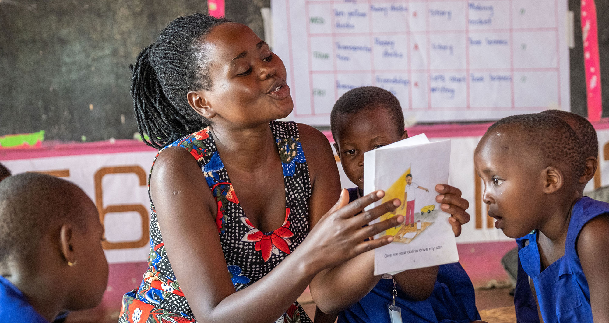A Play Leader reads to children in a Play Lab in Uganda. Photo by Lee Cohen.