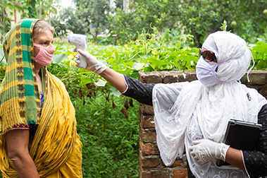 A BRAC community health worker checks a patient's temperature