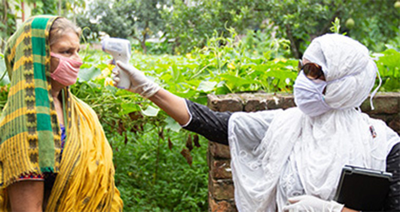 A BRAC community health worker checks a patient's temperature