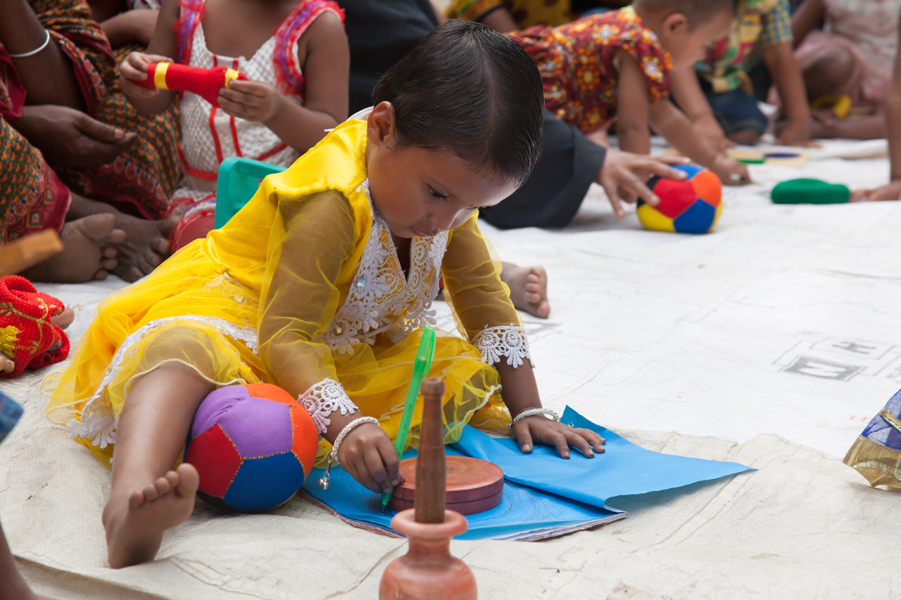 A young girl draws at a Play Lab in Bangladesh.