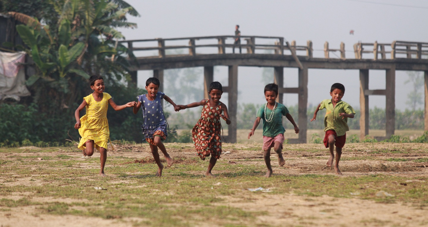 Kids holding hands and running in a field.